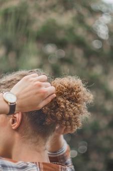 夏の公園で若い縮れ毛の男の肖像