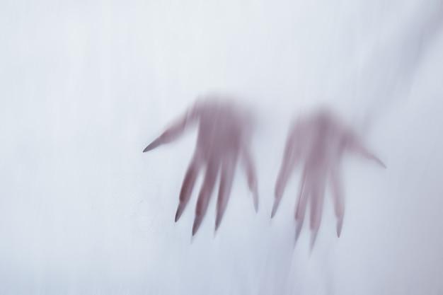 Силуэт женской сексуальной фигуры за туманным стеклом. понятие о духе полтергейста из потустороннего мира. пугающие руки смерти сквозь ткань.