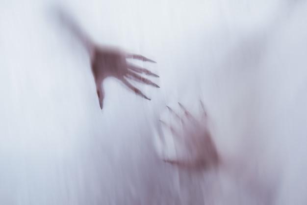 霧のガラスの背後にある女性の性的人物のシルエット。他の世界からのポルターガイストの精神の概念。生地を通して恐ろしい死の手。