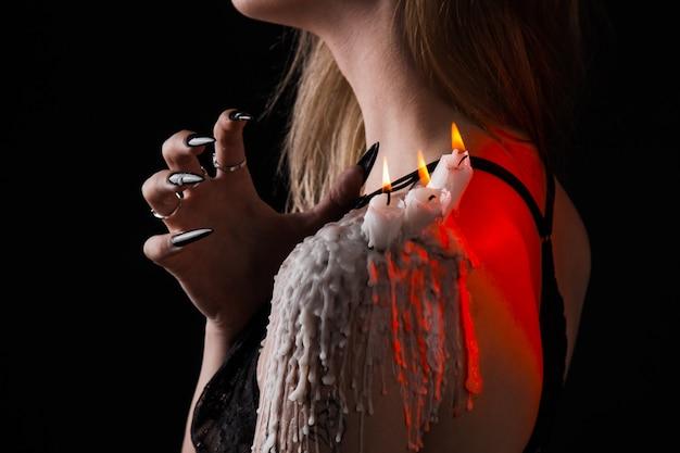 魔女の長い髪の少女が火をつけようとしている