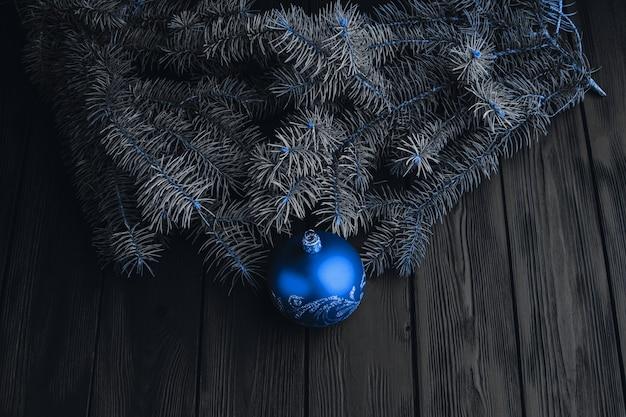 Взгляд сверху рамки ветвей и шариков ели на деревянной предпосылке