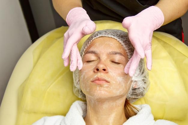 美容のコンセプト。美容師は、スポンジで女性の顔を洗浄し、触れます。