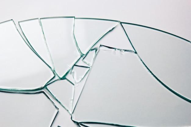 白で隔離あなたのイメージの壊れたガラスの背景。砕けた多くの大きな破片。