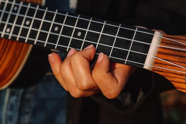 公園のウクレレで長い髪の赤い髪の少女が演じています。学校、音楽教育の概念、学生は弦楽器を演奏することを学びます。ミュージシャンの手、クラシック、メロディー、創造性。