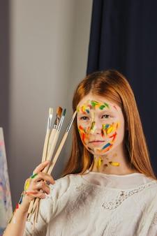 Юная девушка художника в светлом белом платье, рисует картину на холсте в мастерской. лицо окрашено красками. молодой студент использует кисти, холсты и мольберты. творческая работа.
