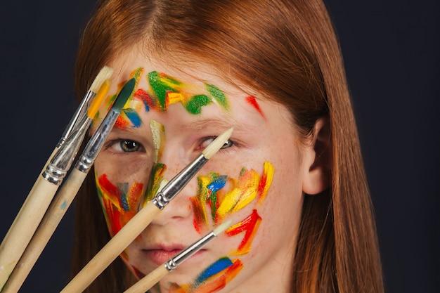 明るい白いドレスを着たアーティストの少女は、ワークショップでキャンバスに絵を描きます。顔は塗料で染色されています。若い学生は、ブラシ、キャンバス、イーゼルを使用します。創造的な仕事。