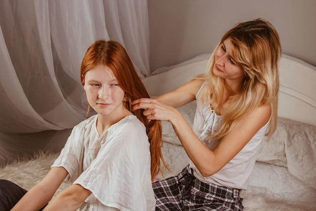 Счастливая семья - улыбающаяся мама заплетает волосы дочери утром после сна в постели. мама собирает дочь в школу. взаимодействие, контакт, любовь.