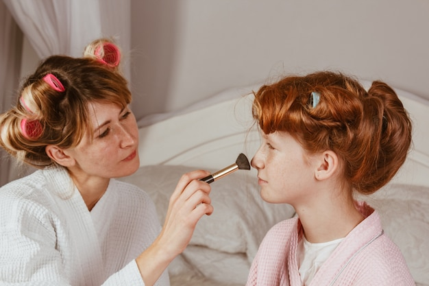 Счастливая семья. молодая красивая мама делает макияж своей красивой дочери на кровати в спальне. рыжая дочь с бигуди на голове смеется.
