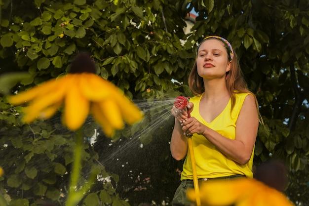 Молодая красивая девушка весело в саду полива растений со шлангом. улыбается, занимаясь любимым хобби.