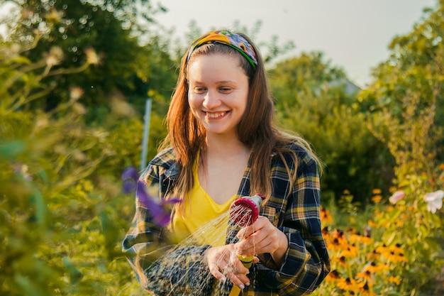 ホースで植物に水をまく庭で楽しんで若いきれいな女の子。好きな趣味をしながら微笑んでいます。
