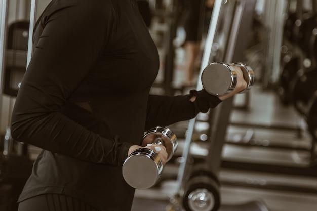 Концепция спорта, фитнеса, культуризма, поднятия тяжестей и людей - близкая вверх женщины изгибая оружия с гантелью в спортзале.
