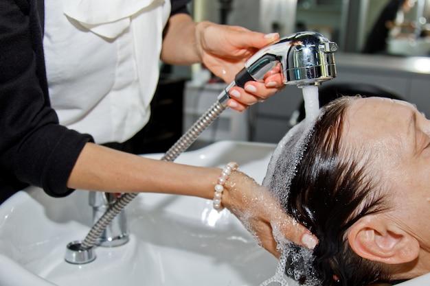 Шикарная жизнерадостная пожилая женщина наслаждается массажем головы, умывая волосы у профессионального парикмахера. уход за красотой, прическа, мода, образ жизни гламур концепции. капли воды и шампунь пены.