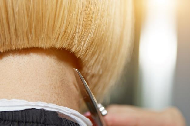 美容師のクローズアップは、サロンでクライアントの濡れた白い髪をカットします。美容師は女性をカットします。ハサミで髪を切る手の側面図です。