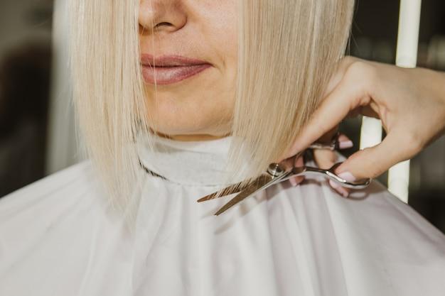 Крупный план парикмахера режет влажные белые волосы клиента в салоне. парикмахер режет женщину. взгляд со стороны волос ручной резки с ножницами.