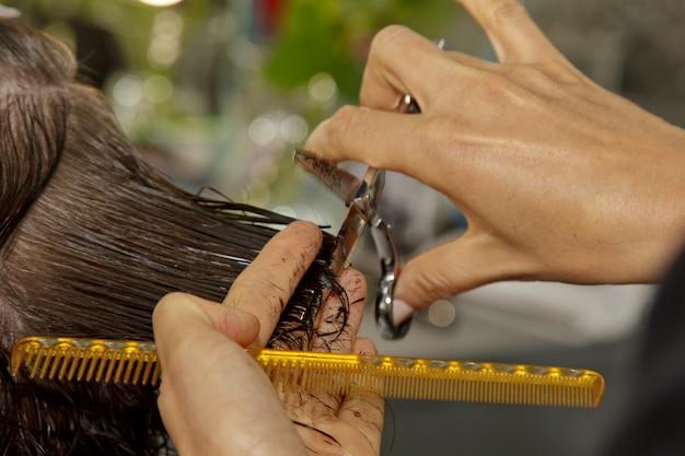 美容院のクローズアップは、サロンでクライアントの濡れた茶色の髪をカットします。美容師は女性をカットします。ハサミで髪を切る手の側面図です。