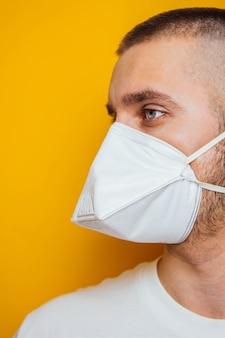 Коронавирус. молодой парень в респираторе на желтом цвете. защита рта и глаз от вирусов, инфекций, выхлопных газов. методы профилактики инфекции.
