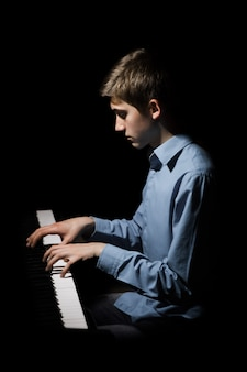 Молодой человек сидит за роялем.