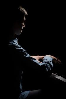 ピアノに座っている若い男。