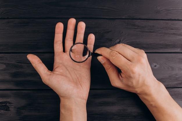 虫眼鏡を保持している素朴な黒い机の上の男性の手。