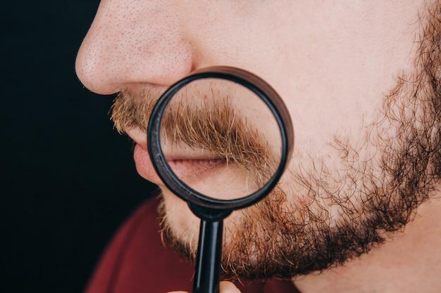 虫眼鏡の下のひげ。男の顔の生え際をクローズアップ。