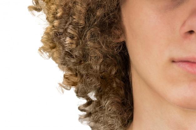長い巻き毛と目を閉じてクローズアップヨーロッパの巻き毛の若いヨーロッパ人男性の半分トリミングされた肖像画に分割。非常に緑豊かな男性の髪の毛。男性のための髪をカーリング。情熱のロック。白い背景で隔離
