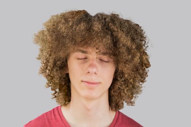 長い巻き毛と目を閉じて若い巻き毛のヨーロッパ人の肖像画は夢を閉じます。非常に緑豊かな男性の髪の毛。男性のための髪をカーリング。情熱のロック