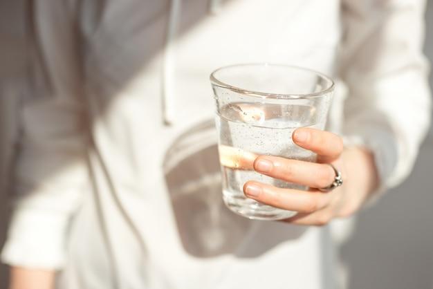 Руки девушки конца-вверх в офисе стоят в солнечном свете держа стекло чистой воды между работой.