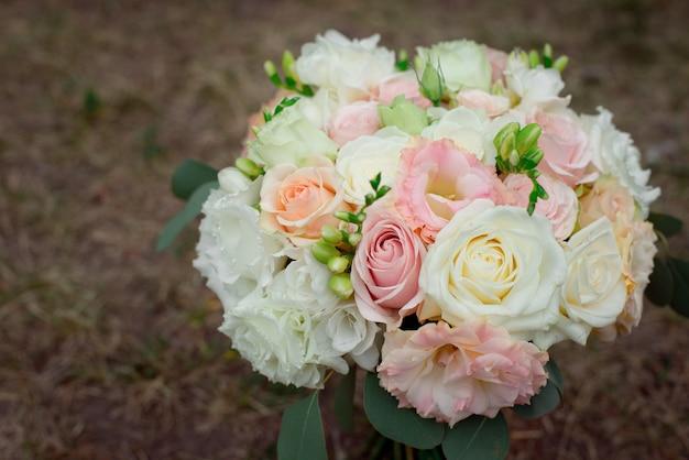 クリーム色のバラとトルコギキョウのぼやけテーブルの美しい繊細なウェディングブーケの側面図です。