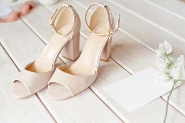 白い花、靴、木製のテーブルの結婚指輪のウェディングブーケ。