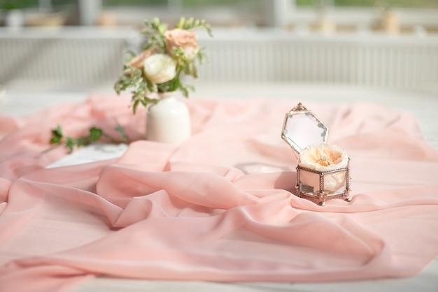 Красивое обручальное кольцо с цветком в стеклянной коробке на таблице.