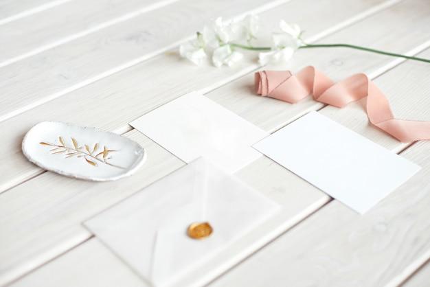 白い花の枝と白い木製のテーブルにスパやケアの装飾が施されたレターカードの結婚式招待状誕生日ギフト券。
