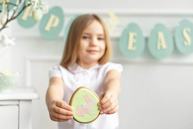 白いシャツを着たかわいい幼児の女の子がクッキーを食べています。