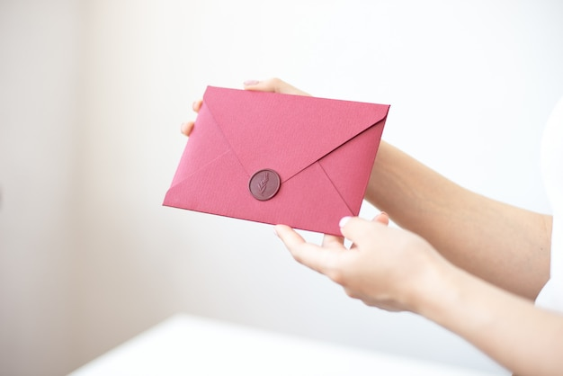 女性は手に招待状を保持します。手のクローズアップの封筒