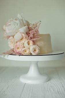 Белый свадебный торт украшенный свежими розами, пионами и зеленью