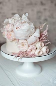 新鮮なバラ、牡丹、緑で飾られた白いウェディングケーキ