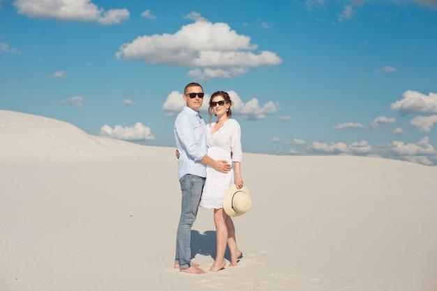 砂丘で夕日を楽しむ若いカップル。ロマンチックな旅行者が砂漠を歩きます。冒険旅行ライフスタイルコンセプト