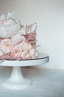 生花、白い裸のケーキ、結婚式、誕生日、イベント用のスタイリッシュなケーキで飾られました