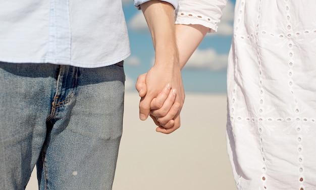 Конец-вверх молодой пары наслаждаясь заходом солнца в дюнах держа руки. романтический путешественник гуляет по пустыне. концепция приключенческого путешествия