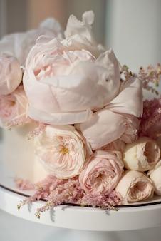 ピンクのバラの花と白い牡丹の丸い甘い白いクリームケーキ