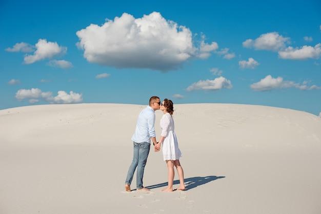Романтическая влюбленная пара целуется на белом песке в пустыне