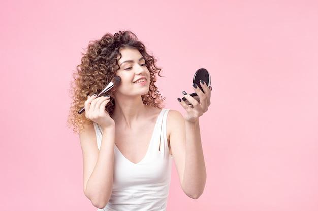 陽気な若い女性のプロファイルは手鏡で立っていると彼女の鼻を粉に