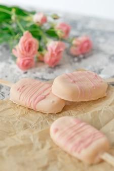 Изысканный десерт из мороженого с кокосовой глазурью и шоколадной глазурью розового шоколада из домашней пекарни на сером фоне.