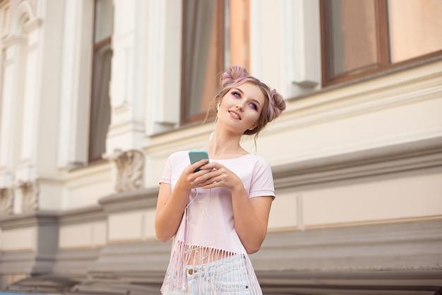 ヘッドフォンで音楽を聴いて旅行トレンディな衣装、ピンクの髪型パンに身を包んだ通りを歩いて若いスタイリッシュな流行に敏感な女性の肖像画