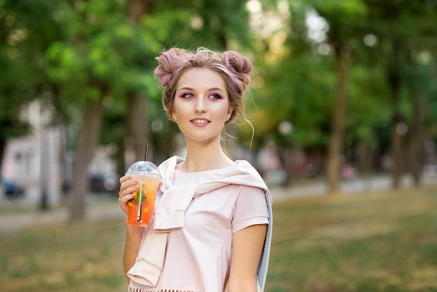 Молодая красивая девушка, пить свежий сок из пластиковых вынос чашки пищи после прогулки на открытом воздухе. здоровый образ жизни. улыбается стройная блондинка с розовыми волосами.