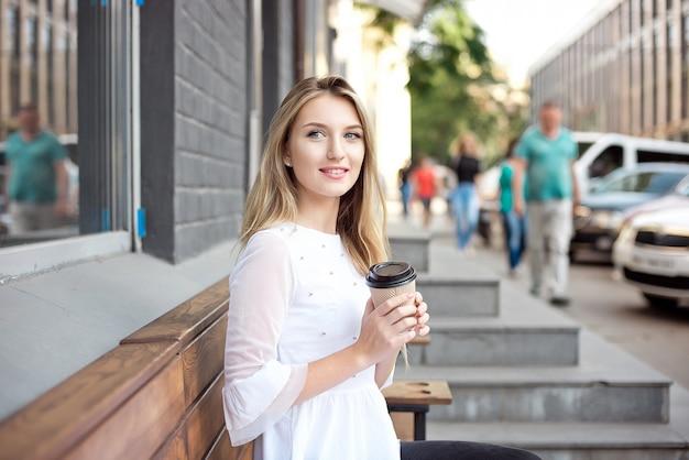 街を歩いて飲む美しい少女は、屋外カフェでコーヒーを奪います。市の朝のシーン。