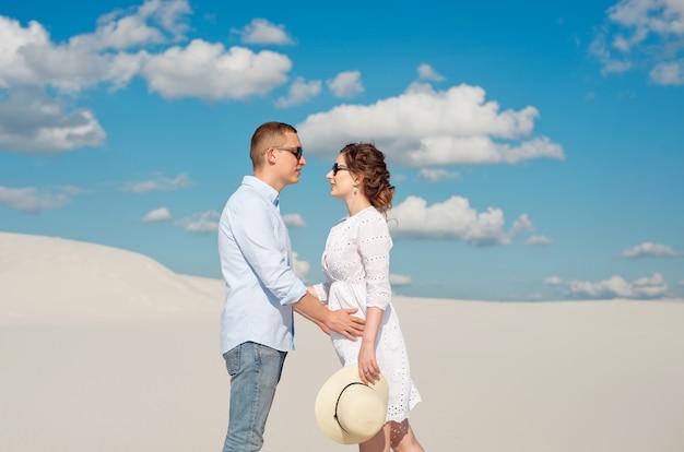 砂丘で夕日を楽しむ若いカップル。ロマンチックな旅行者は砂漠を歩きます。