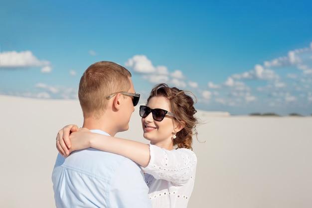 砂丘で夕日を楽しむ若いカップル。ロマンチックな旅行者は砂漠を歩きます。冒険旅行ライフスタイルコンセプト