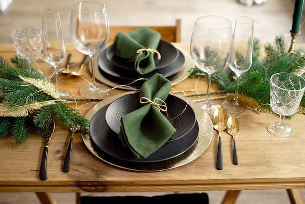 松の枝、テーブルの設定、暗いクリスマスツリーの背景の上のろうそくのクリスマスの装飾