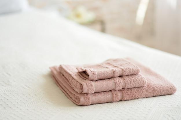 Сложенные полотенца на кровати в номере.