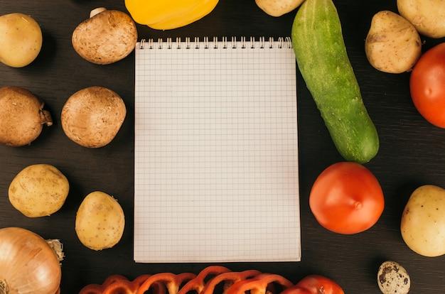 ショッピングリスト、レシピ本、ダイエットプラン。新鮮な生野菜、果物、調理用食材。上面図